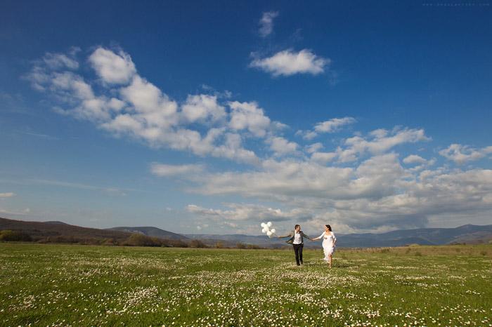Масштабная свадебная фотография жениха и невесты бегущих по холму с белыми шариками