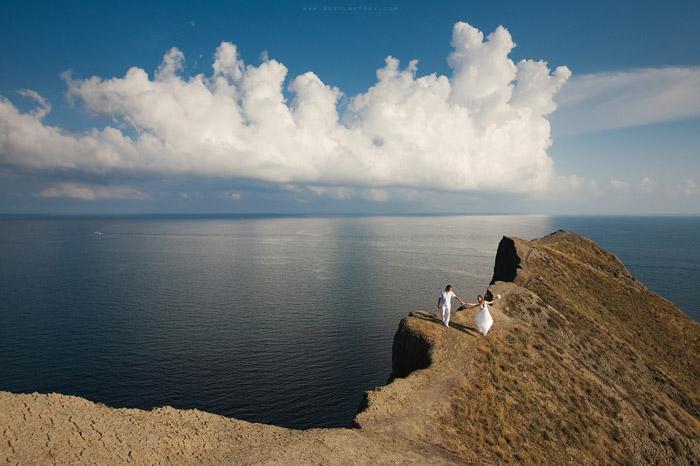 Свадебный фотограф Олег Бреславцев. Жених и невеста на хребте горы над морем